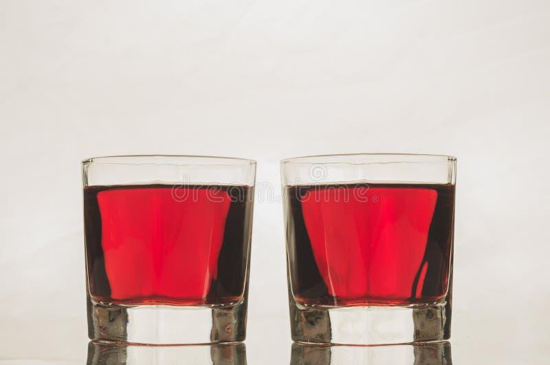 Vidros com bebida/vidros vermelhos com bebida vermelha em um backgro branco imagem de stock