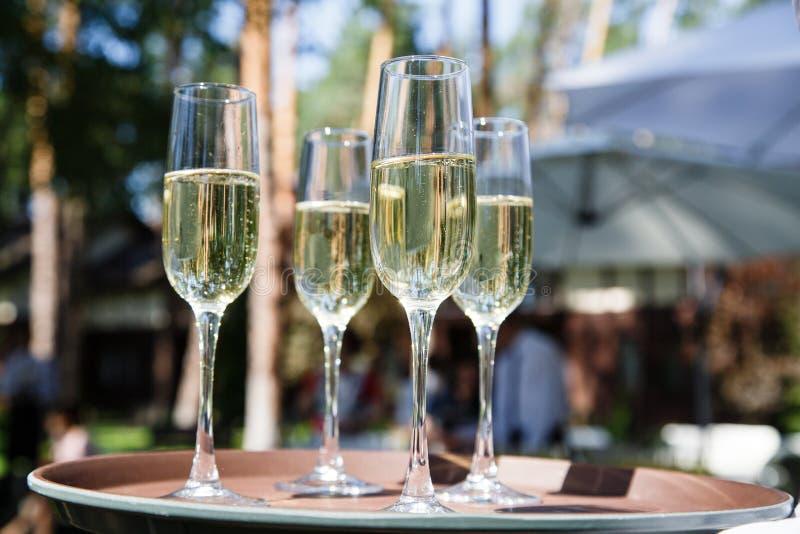 Vidros com champanhe em um outdor do casamento fotografia de stock