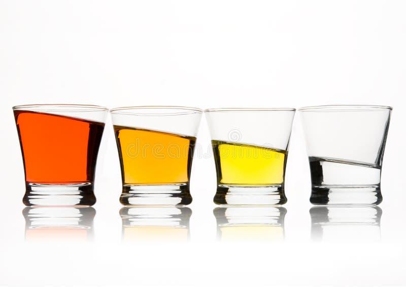 Vidros com líquido colorido no fundo branco imagens de stock