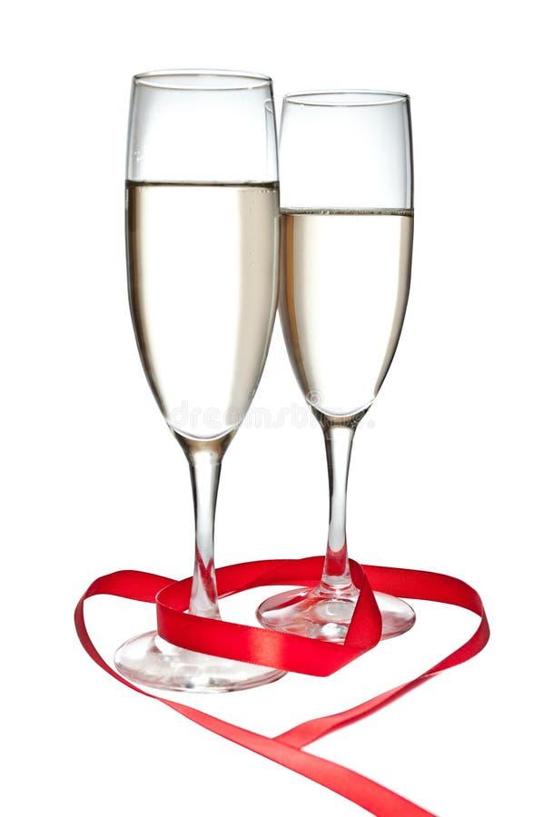 Vidros com o Champagne e a fita vermelha isolados imagens de stock