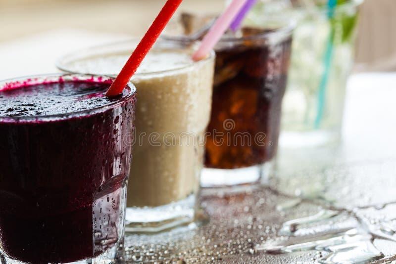 Vidros com os cocktail com palhas no borrado imagem de stock