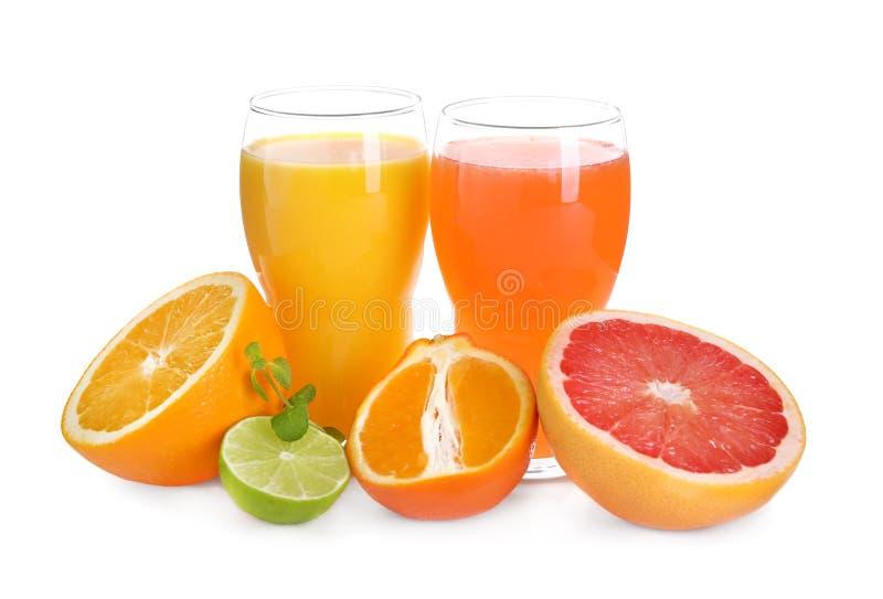 Vidros com suco delicioso do citrino e frutos frescos no fundo branco fotografia de stock