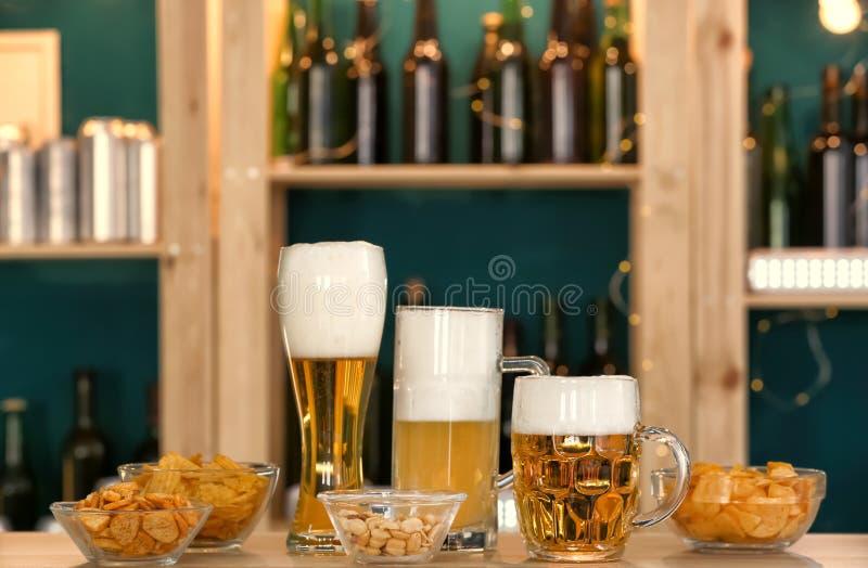 Vidros com tipos diferentes de cerveja e de petiscos na tabela na barra fotos de stock