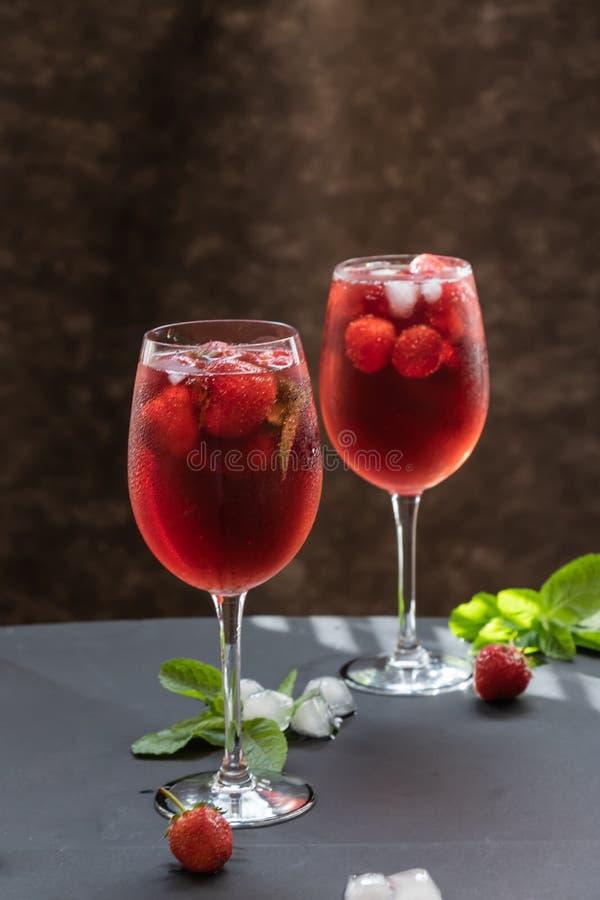 Vidros com uma bebida de refrescamento com morangos e hortelã em uma tabela imagem de stock