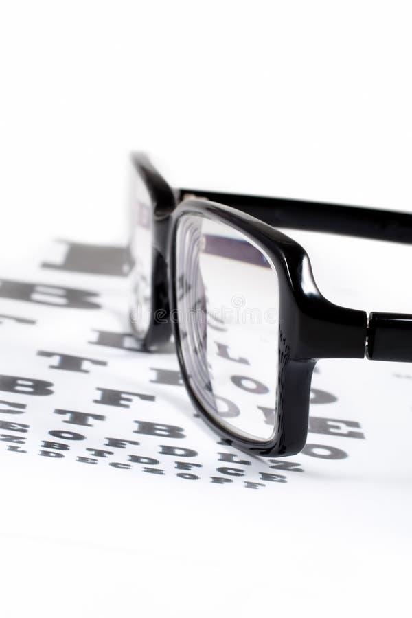 Vidros com VERIFICAÇÃO da TABELA DA VISTA imagem de stock royalty free