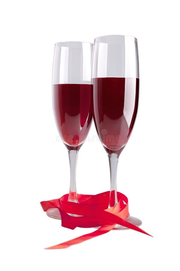 Vidros com vinho vermelho e a fita vermelha isolados foto de stock royalty free