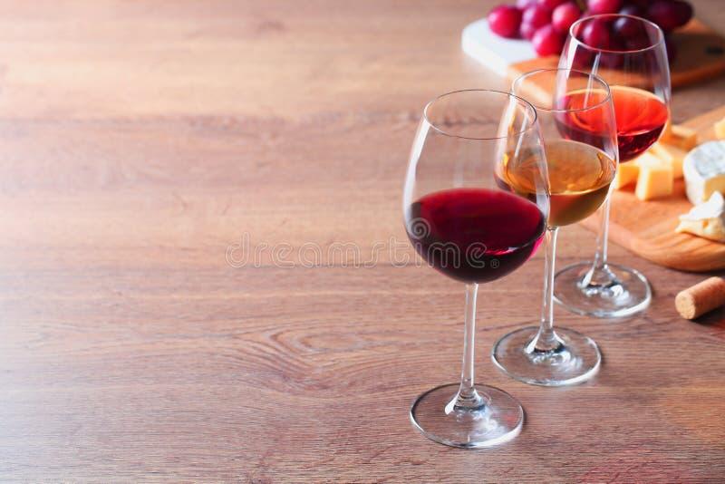 Vidros com vinhos e os aperitivos diferentes na tabela de madeira fotos de stock royalty free