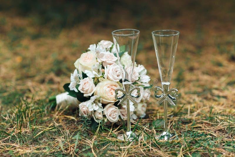 Vidros comemorativos do casamento um par do recém-casado com um ramalhete em um fundo natural homogêneo Conceito do casamento imagens de stock