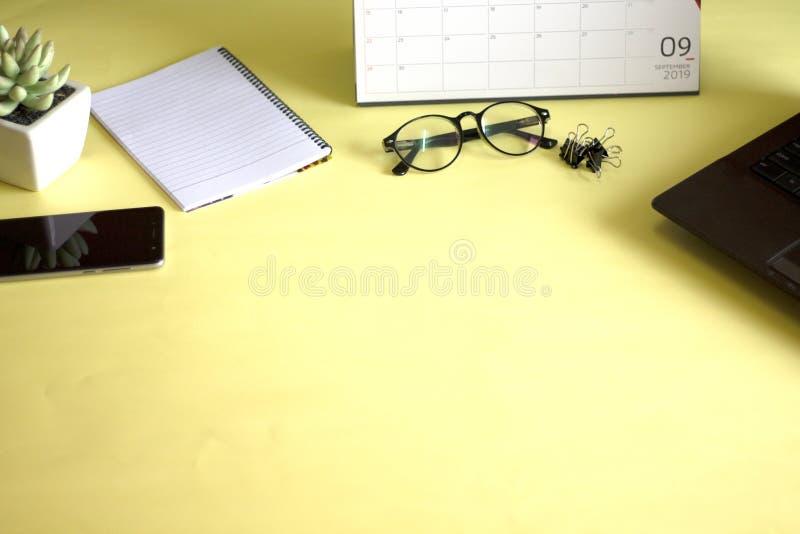 Vidros, computador e cadernos da pena colocados em um fundo amarelo Conceito de trabalho foto de stock royalty free