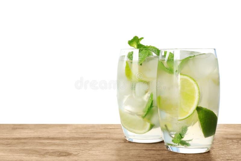 Vidros da bebida de refrescamento com fatias do cal e da hortelã na tabela de madeira imagem de stock