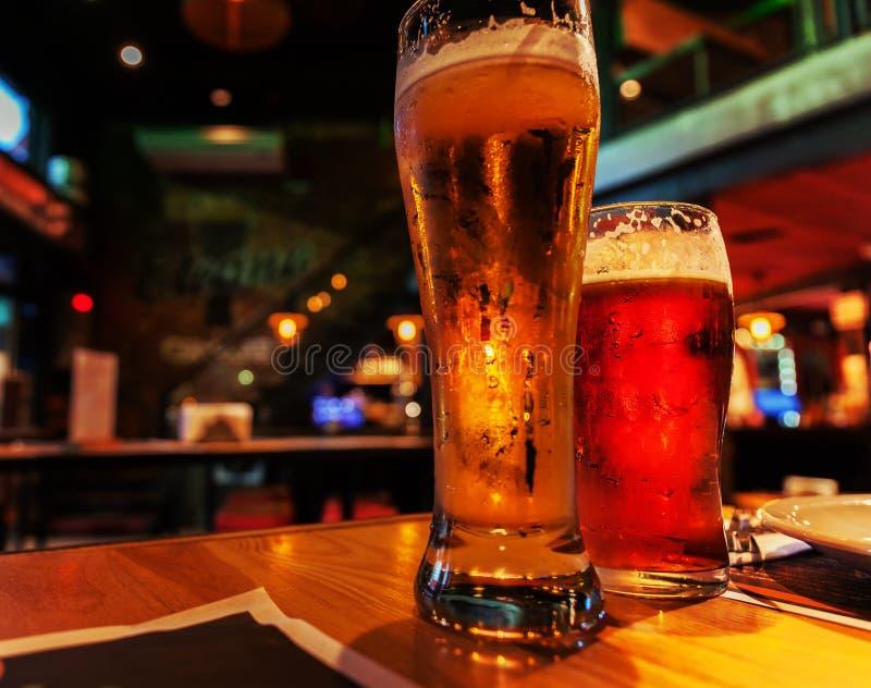 Vidros da cerveja clara e escura em um fundo do bar Ajuste crepuscular atmosférico na barra foto de stock