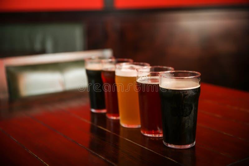 Vidros da cerveja diferente na tabela imagens de stock