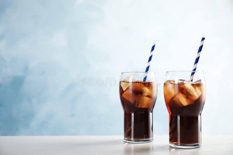 Vidros da cola de refrescamento com cubos e palhas de gelo na tabela foto de stock