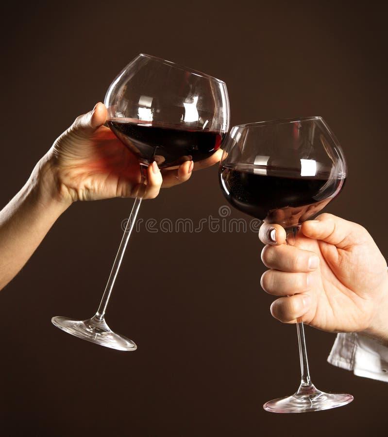 Vidros da terra arrendada dos povos do vinho vermelho imagens de stock