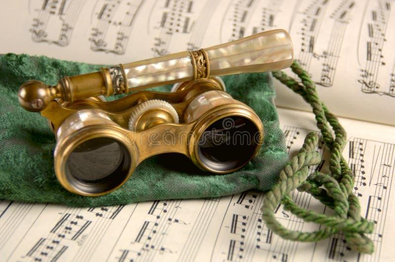 Vidros de ópera antigos na música de folha fotografia de stock