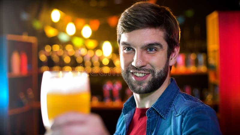 Vidros de cerveja masculinos farpados consideráveis com amigo, resultados do tinido do fim de semana no bar foto de stock