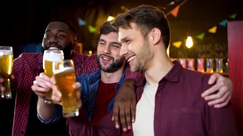 Vidros de cerveja multi-étnicos bebidos do tinido dos amigos, passando o tempo no bar, partido imagem de stock