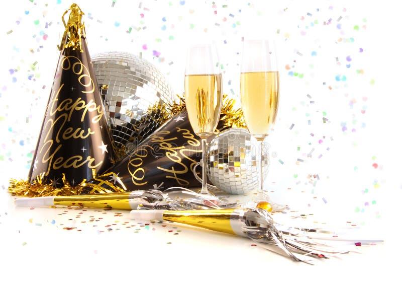 Vidros de Champagne com os chapéus festivos do partido no branco