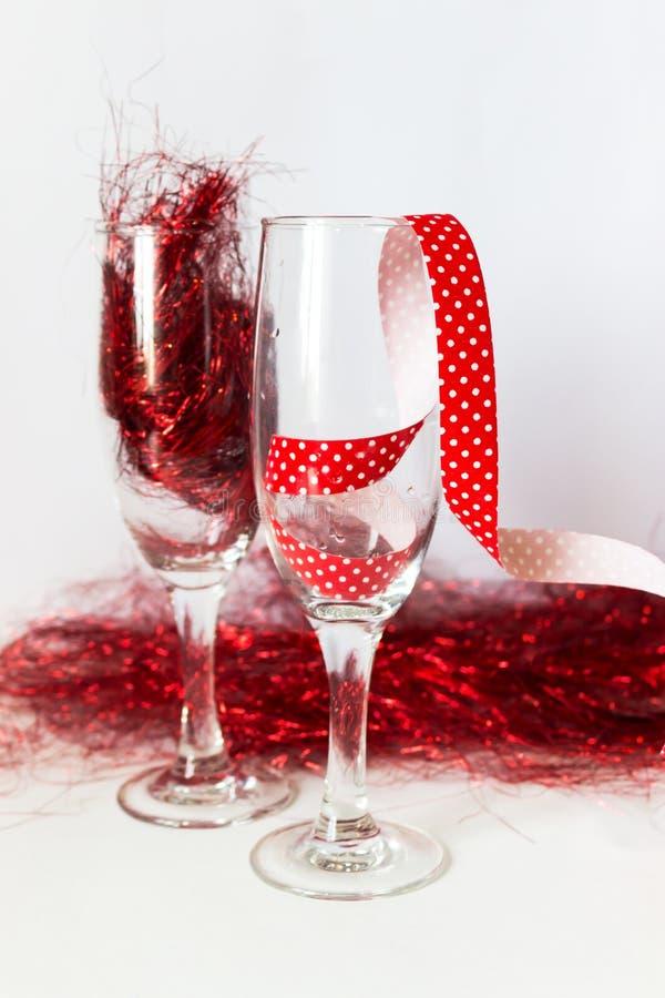 Vidros de Champagne com uma fita serpentina festiva no fundo brilhante do ouropel Conceito do ano novo ou do Natal imagem de stock royalty free