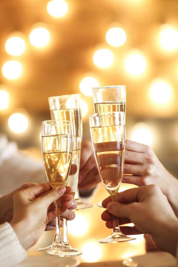 Vidros de Champagne nas mãos no fundo dourado foto de stock royalty free