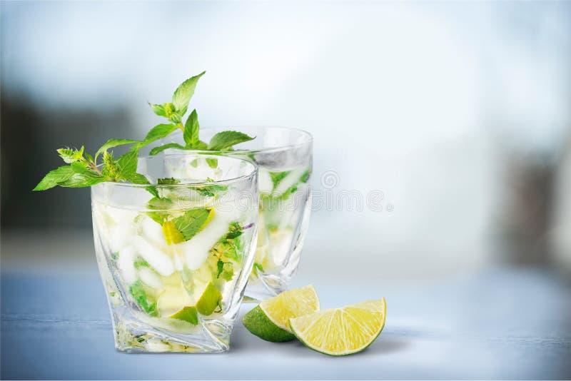 Vidros de cocktail deliciosos com cal no cinza fotografia de stock royalty free