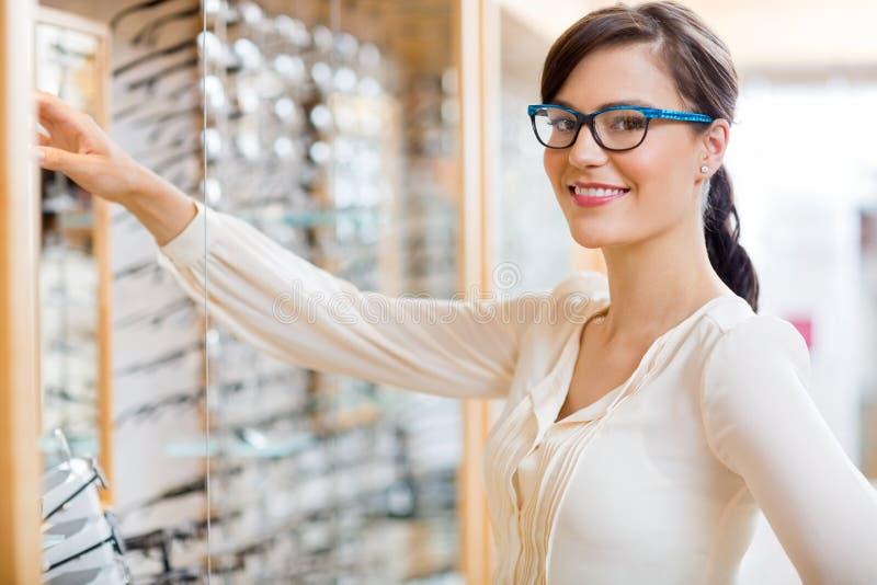 Vidros de compra da mulher feliz no ótico Store imagem de stock royalty free