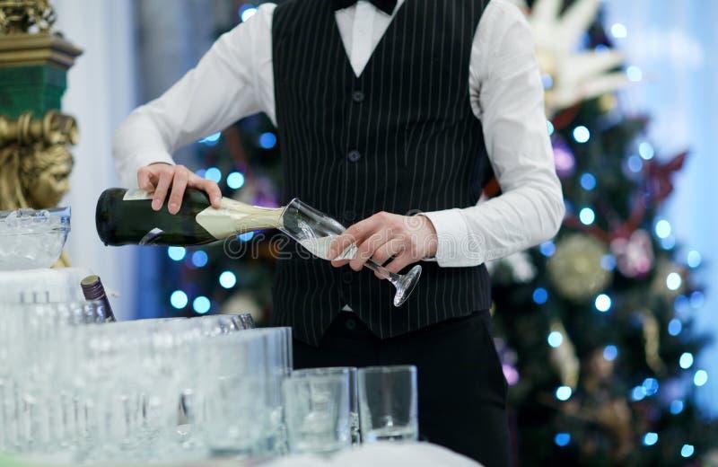 Vidros de derramamento do garçom do champanhe imagem de stock royalty free