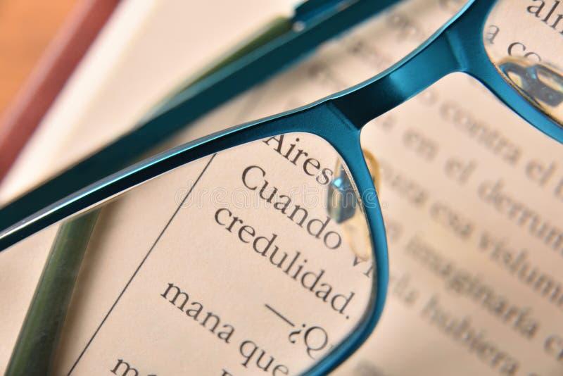 Vidros de leitura azuis no fim aberto do livro acima fotografia de stock
