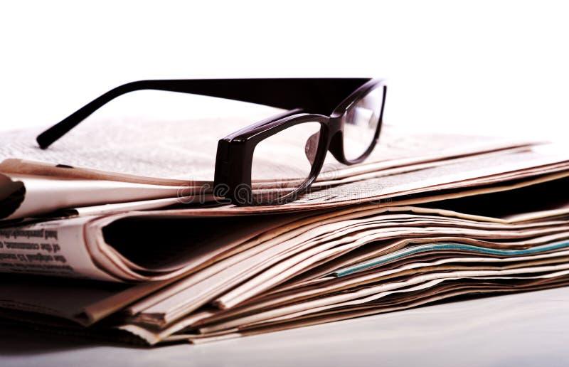 Vidros de leitura em jornais fotos de stock