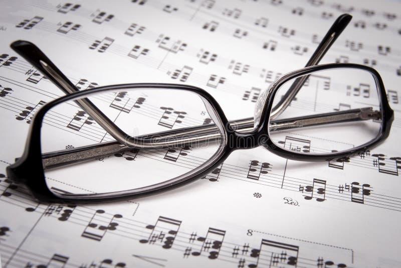 Vidros de leitura sobre as folhas de música imagem de stock royalty free
