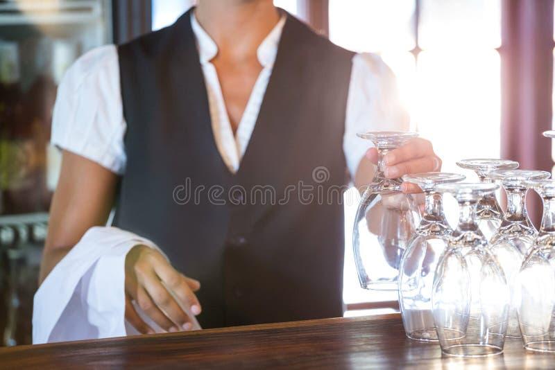 Vidros de limpeza da empregada de mesa fotografia de stock