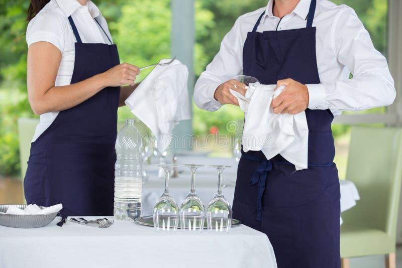 Vidros de limpeza da empregada de mesa e do garçom no restaurante imagem de stock