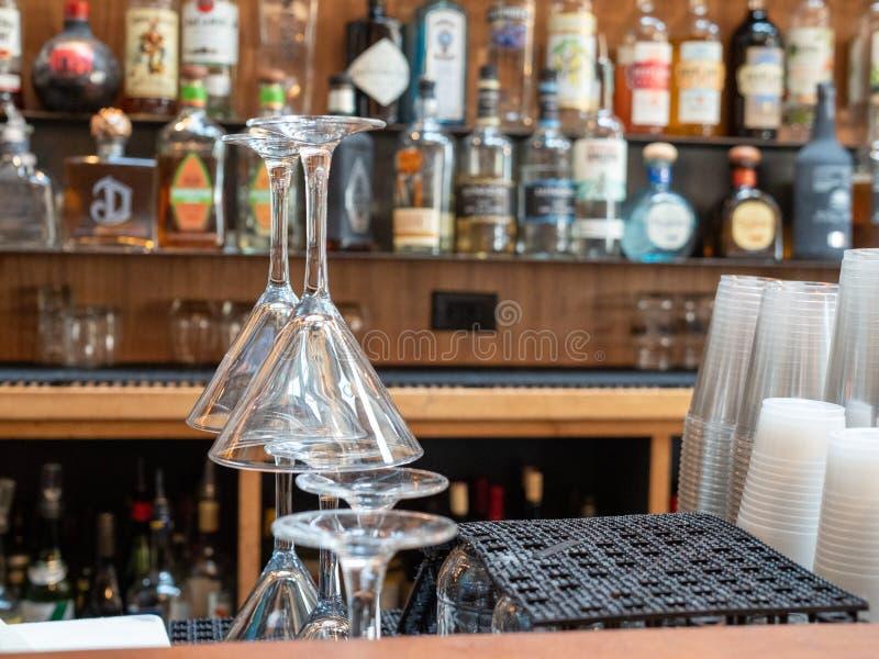 Vidros de Martini empilhados atrás de uma barra ocupada com copos e licor plásticos fotos de stock