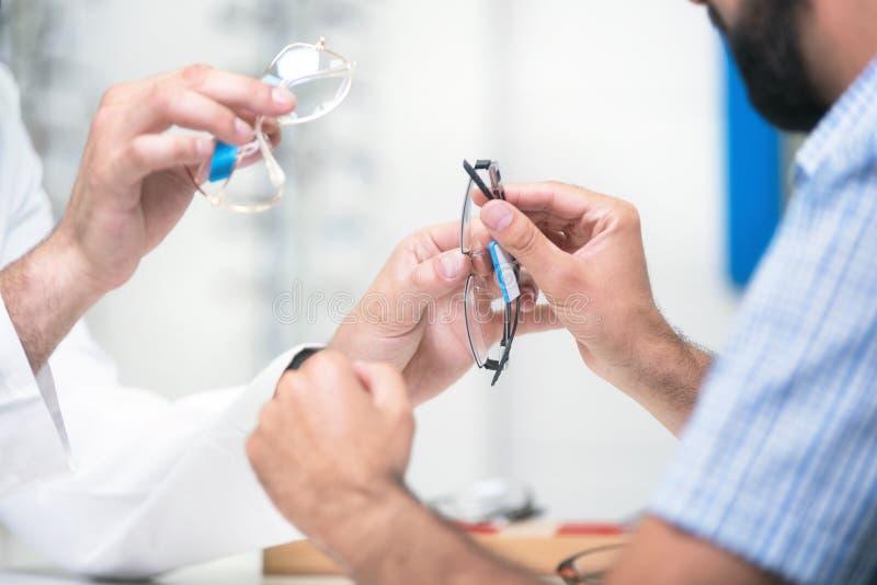 Vidros de oferecimento do ótico ao cliente para testar e tentar Doutor de olho que mostra lentes pacientes na loja dos espet?culo fotografia de stock royalty free
