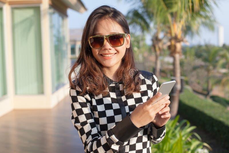 Vidros de sol vestindo da mulher asiática nova e telefone esperto à disposição a fotos de stock