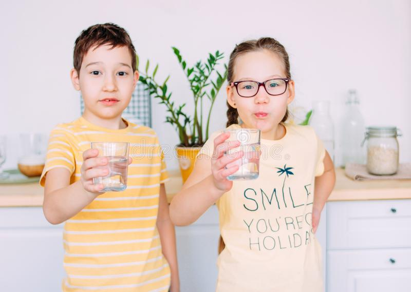 Vidros de sorriso da posse do menino e da menina da agua potável nas mãos, foco seletivo foto de stock royalty free
