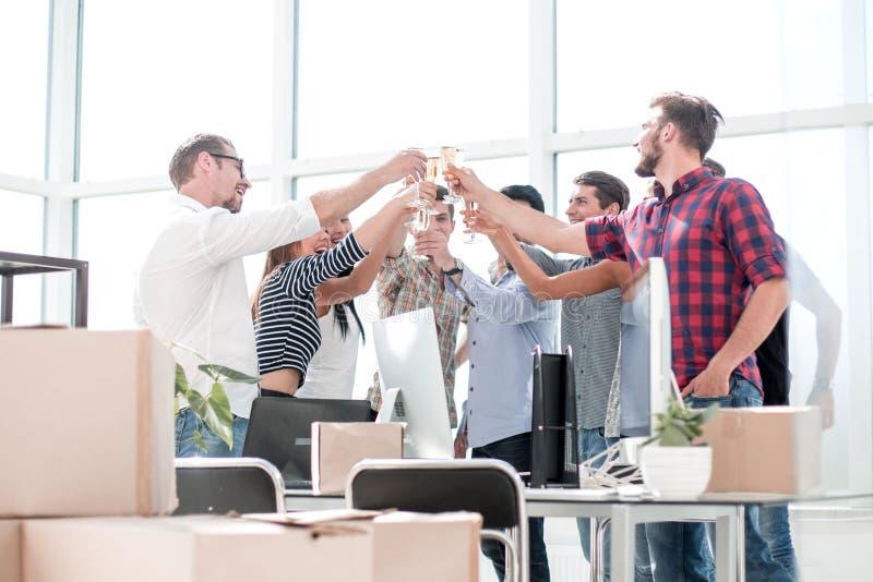 Vidros de sorriso do tinido do businessteam, comemorando o sucesso no escritório fotografia de stock