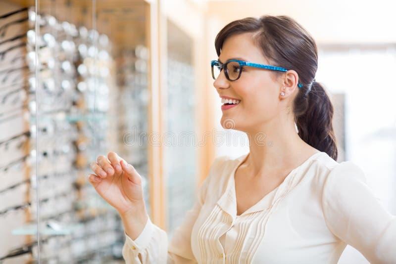 Vidros de tentativa da mulher feliz no ótico Store imagens de stock