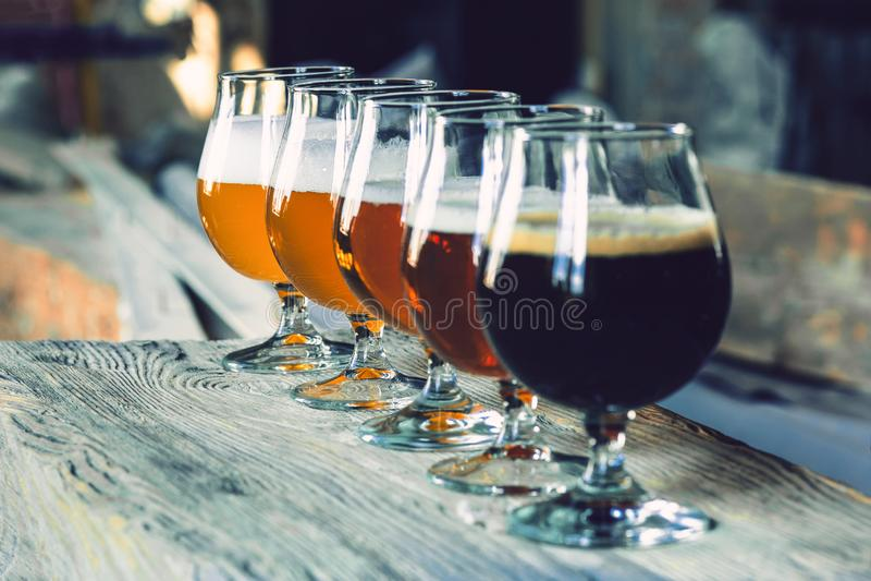 Vidros de tipos diferentes da cerveja no fundo de madeira fotos de stock royalty free