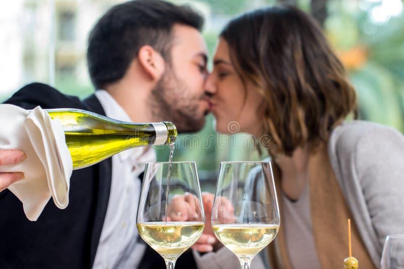 Vidros de vinho branco com pares no fundo imagens de stock