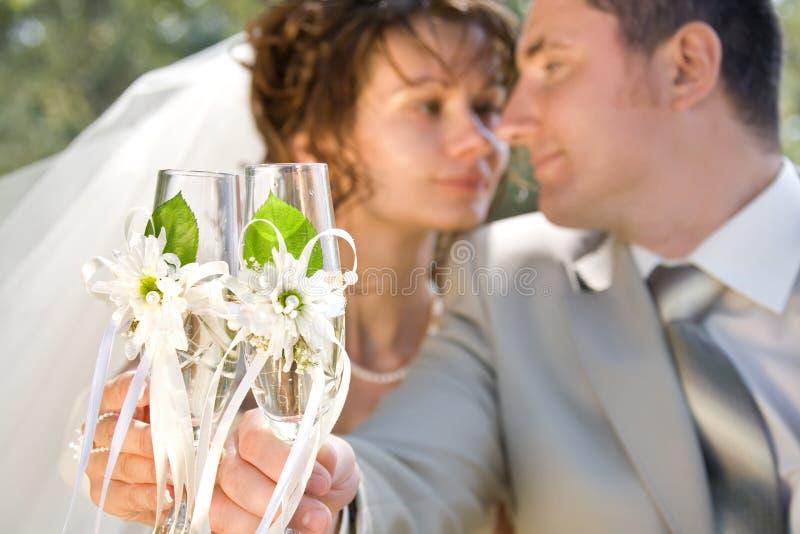 Vidros de vinho da terra arrendada da noiva e do noivo imagens de stock royalty free