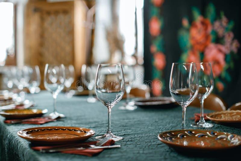 Vidros de vinho e serviço da tabela no restaurante rústico do estilo fotografia de stock
