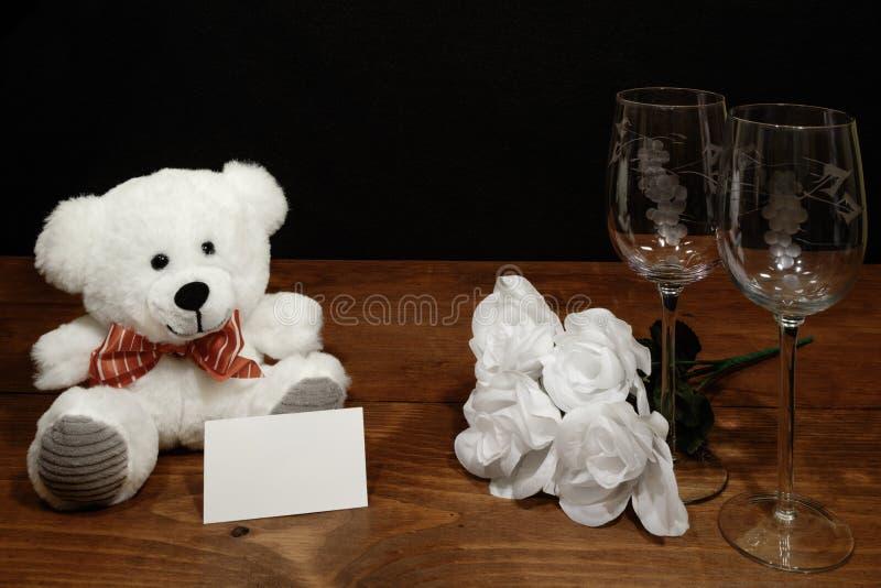 Vidros de vinho gravados bonitos com rosas brancas e o urso de peluche branco e etiqueta do nome na tabela de madeira e no fundo  imagens de stock