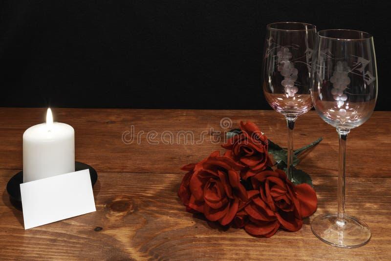 Vidros de vinho gravados bonitos com rosas vermelhas e vela branca na tabela de madeira e no fundo escuro imagem de stock