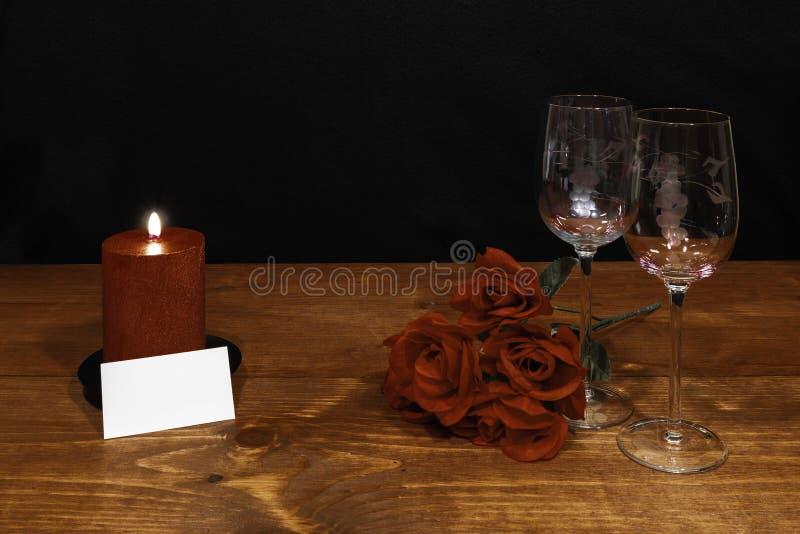 Vidros de vinho gravados bonitos com rosas vermelhas e vela vermelha na tabela de madeira e no fundo escuro fotos de stock