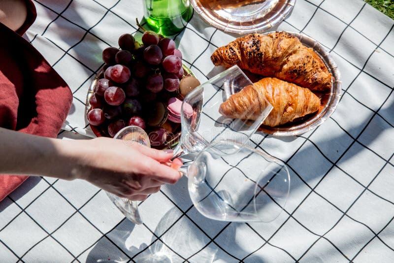 Vidros de vinho guardando f?meas por uma data na maca verificada com uva e croissant imagem de stock