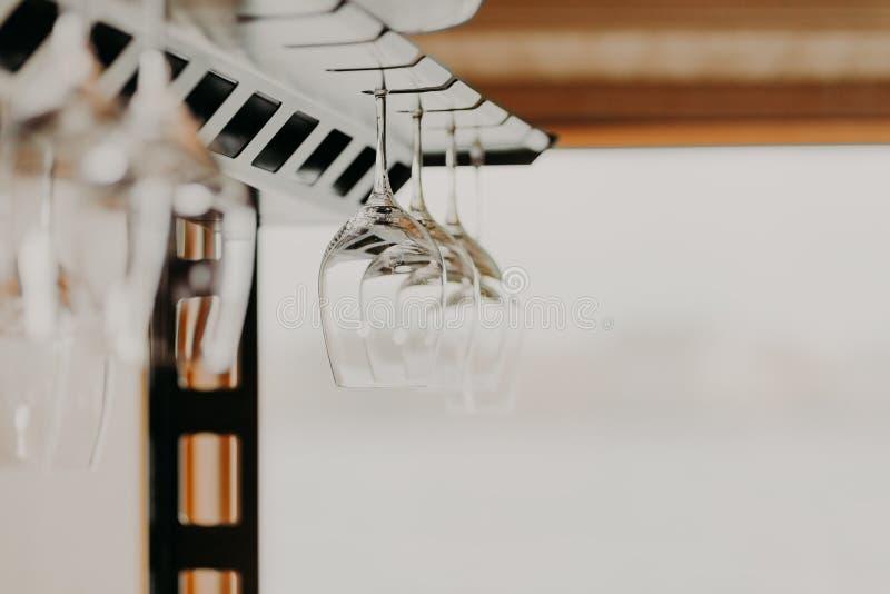 Vidros de vinho vazios que penduram na cremalheira da barra, foto com fundo borrado fotografia de stock royalty free