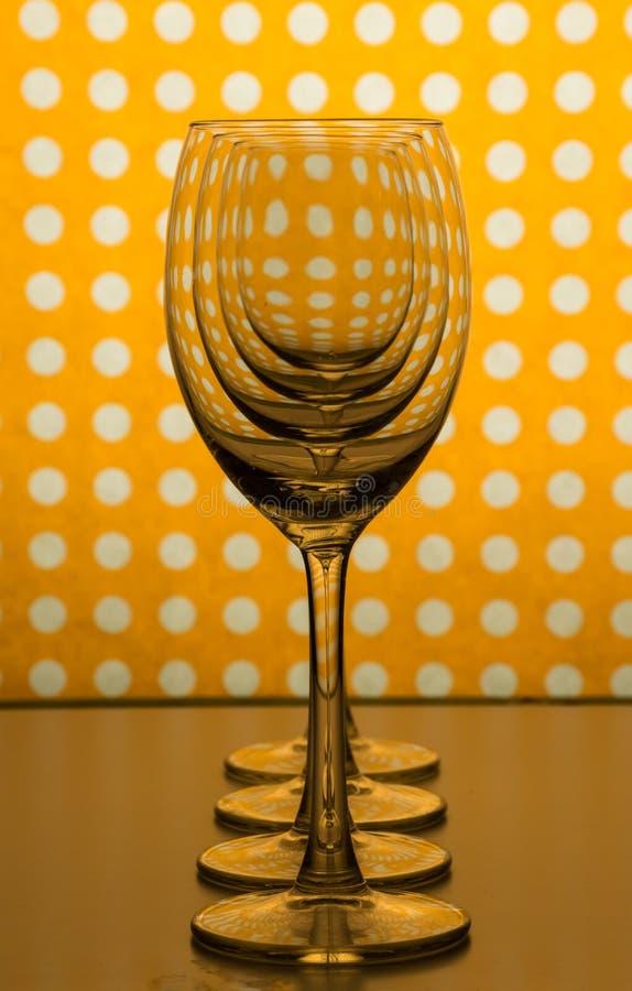 Vidros de vinho vazios transparentes um atrás do outro e fundo alaranjado amarelo com pontos brancos imagem de stock royalty free