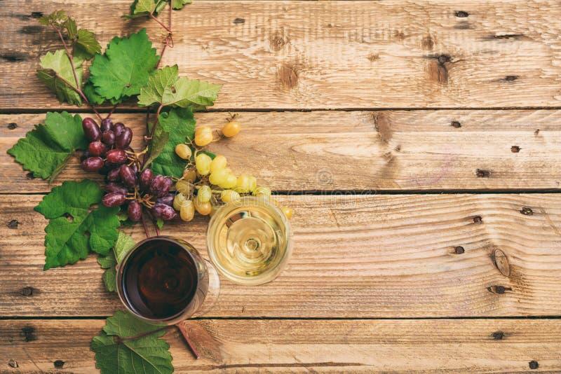 Vidros de vinho vermelho e branco e uvas frescas no fundo de madeira, espaço da cópia imagens de stock