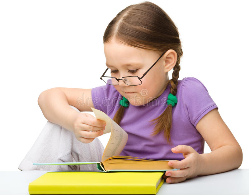 Vidros desgastando bonitos do livro de leitura da menina fotos de stock royalty free